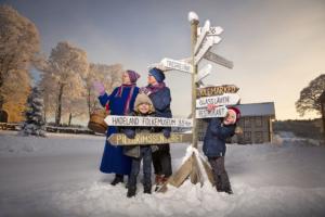 Barn og voksne ved skilt i vinterkledd landskap på Granavollen. Skiltene perker mot julemarked på Historiske Hadeland.